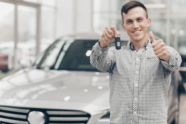Junger mann, der neues auto an der verkaufsstelle kauft Premium Fotos