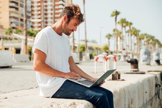 Junger mann, der notizbuch im freien hält Kostenlose Fotos