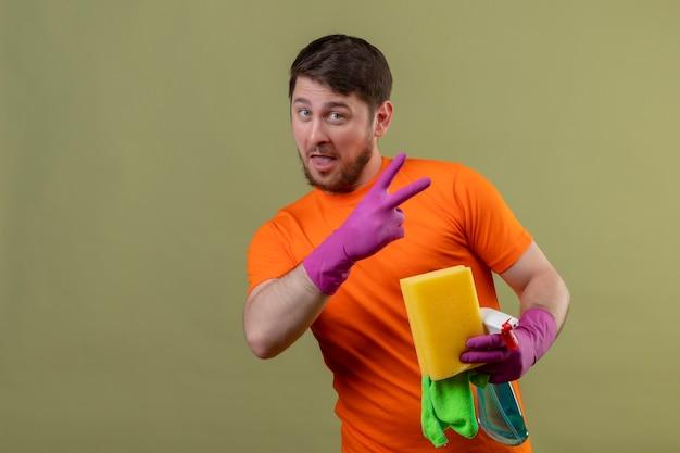 Junger mann, der orange t-shirt und gummihandschuhe trägt, die reinigungswerkzeuge souverän und glücklich halten, nummer zwei oder siegeszeichen zeigend über grüner wand zeigend Kostenlose Fotos