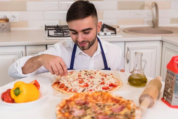 Junger mann, der pizza in der küche kocht Kostenlose Fotos