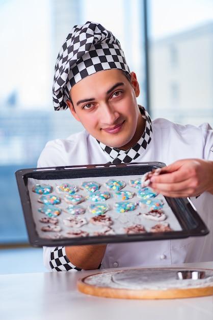 Junger mann, der plätzchen in der küche kocht Premium Fotos