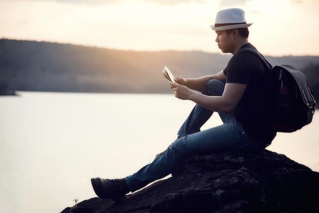 Junger mann der reise bei sonnenuntergang Kostenlose Fotos