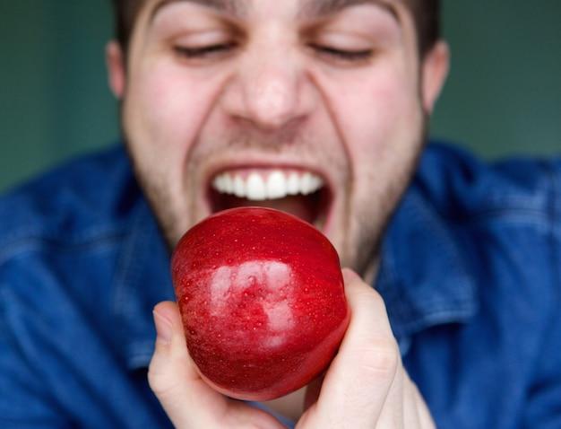 Junger mann, der roten apfel isst Premium Fotos
