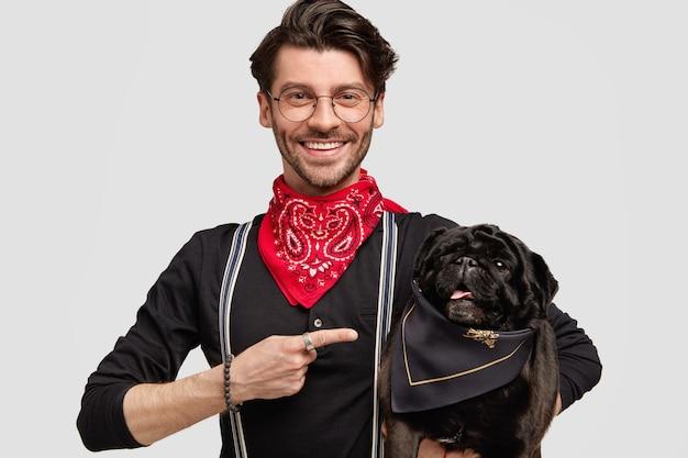 Junger mann, der rotes halstuch und schwarzes hemd hält hund hält Kostenlose Fotos