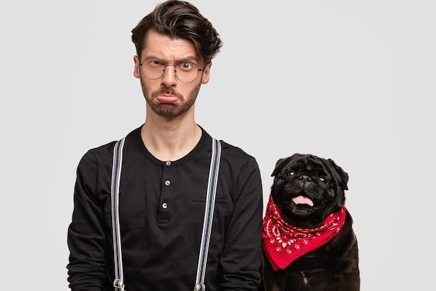 Junger mann, der rotes kopftuch und schwarzes hemd und seinen hund trägt Kostenlose Fotos