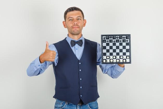 Junger mann, der schachbrett mit daumen oben im anzug hält Kostenlose Fotos