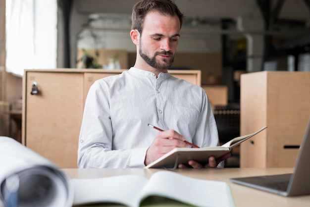 Junger mann, der schreiben auf tagebuch im büro hält Kostenlose Fotos
