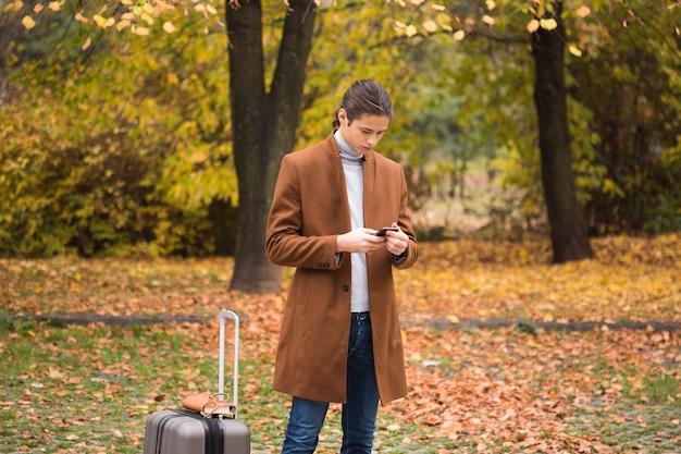 Junger mann, der sein telefon im park überprüft Kostenlose Fotos