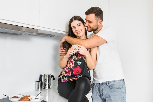 Junger mann, der seine freundin in der hand hält kaffeetasse umfasst Kostenlose Fotos