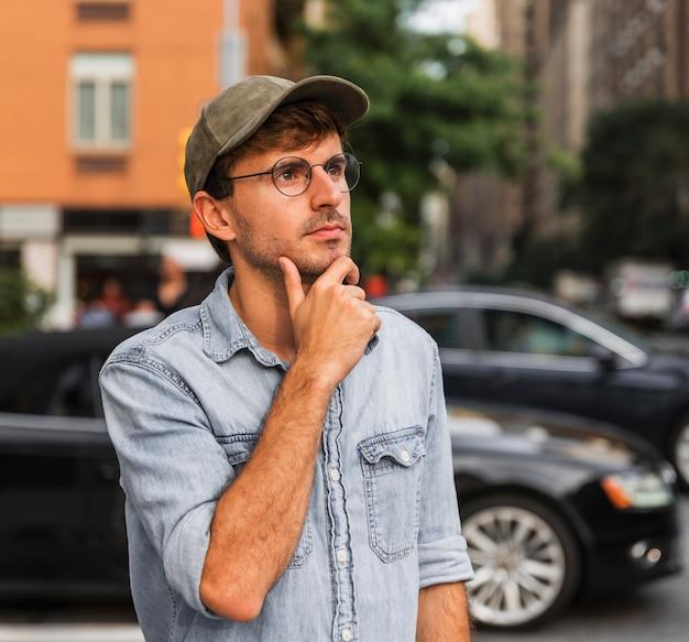Junger mann, der seine hand unter seinem bart hält Kostenlose Fotos