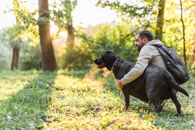 Junger mann, der seinen schoßhund im garten hält Kostenlose Fotos