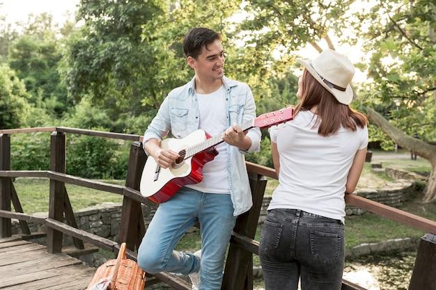 Junger mann, der seiner freundin gitarre spielt Kostenlose Fotos