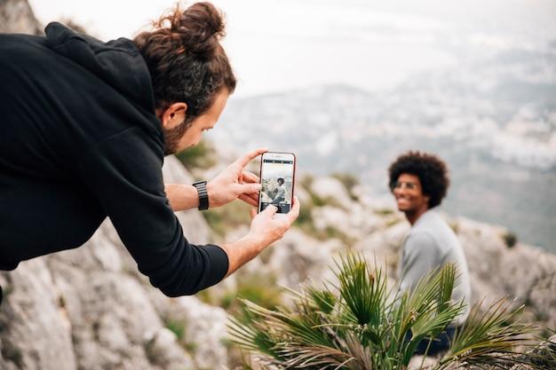 Junger mann, der selfie seines freundes sitzt auf dem berg nimmt Kostenlose Fotos