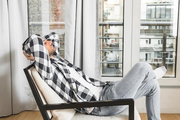 Junger mann, der sich zu hause auf stuhl entspannt Kostenlose Fotos