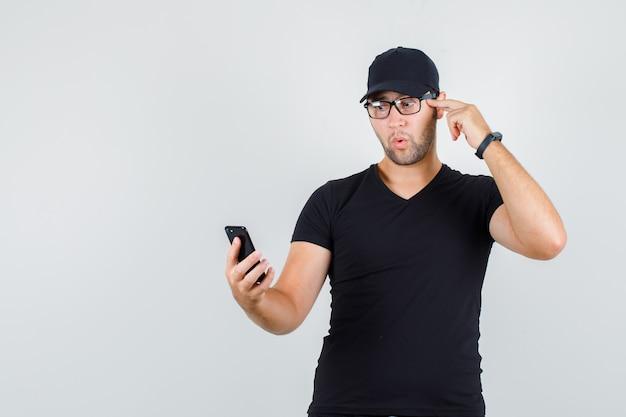 Junger mann, der smartphone mit finger auf schläfen im schwarzen t-shirt betrachtet Kostenlose Fotos