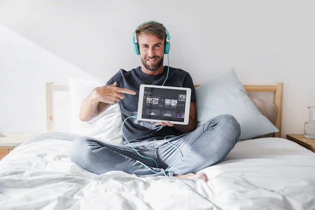 Junger mann, der tablette mit spotify app hält Kostenlose Fotos