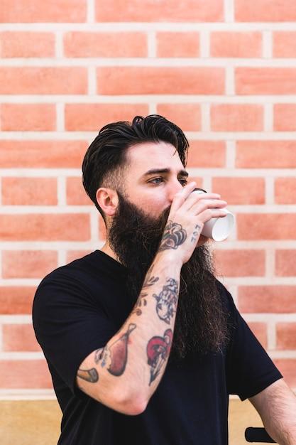 Junger mann, der tätowierung auf seinem handtrinkenden kaffee gegen backsteinmauer hat Kostenlose Fotos