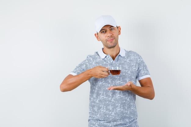 Junger mann, der tasse tee im t-shirt und in der mütze hält und fröhlich schaut Kostenlose Fotos