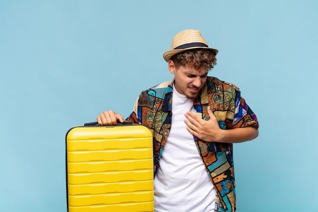 Junger mann, der traurig, verletzt und mit gebrochenem herzen aussieht, beide hände nah am herzen hält, weint und sich deprimiert fühlt. urlaubskonzept Premium Fotos