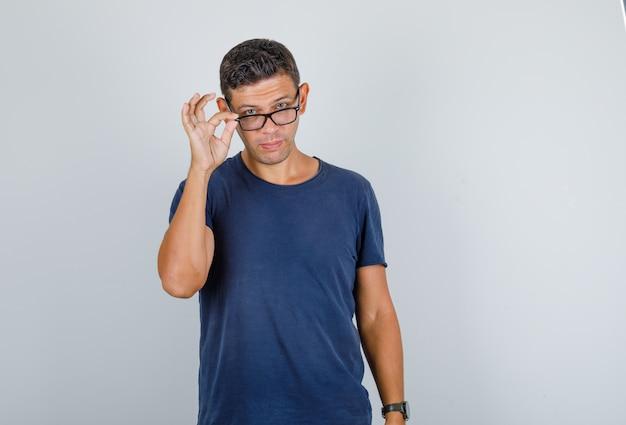 Junger mann, der über brille im dunkelblauen t-shirt, vorderansicht späht. Kostenlose Fotos