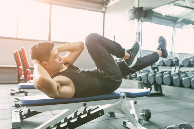 Junger mann, der übung, sit-ups und kreuzknirschen für bauchmuskeln im fitnessclub oder in g macht Premium Fotos