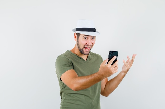 Junger mann, der video-chat im grünen t-shirt und im hut hat und erstaunt schaut Kostenlose Fotos