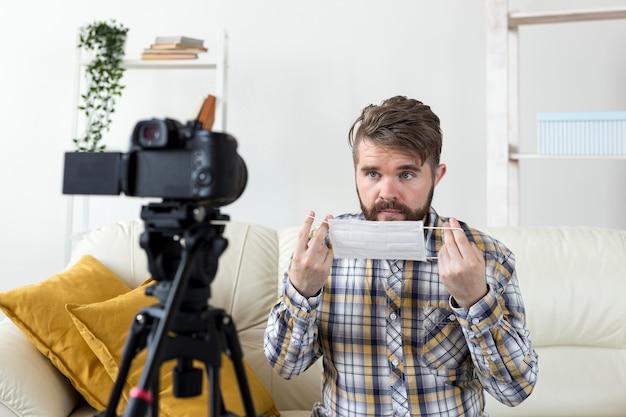 Junger mann, der video zu hause mit gesichtsmaske aufzeichnet Kostenlose Fotos