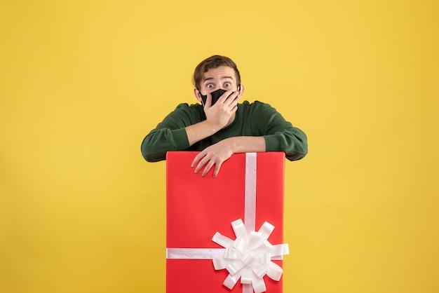 Junger mann der vorderansicht, der hand zu seinem mund hinter großer geschenkbox auf gelb setzt Kostenlose Fotos