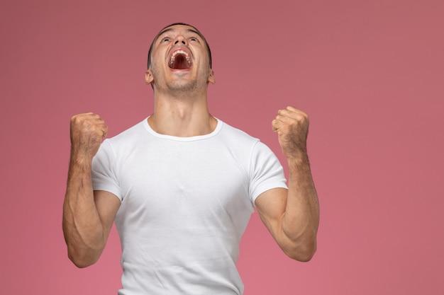 Junger mann der vorderansicht im weißen hemd, das sich emotional auf dem rosa hintergrund freut Kostenlose Fotos