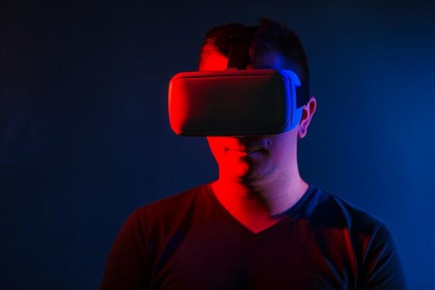 Junger mann, der vr-kopfhörer trägt und virtuelle realität erlebt. Kostenlose Fotos