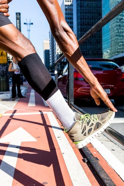 Junger mann des athleten, der sein bein und hand auf bürgersteig in der stadt ausdehnt Kostenlose Fotos