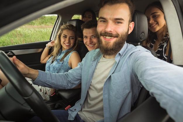 Junger mann des bartes, der mit seinem freund im auto nimmt selfie sitzt Kostenlose Fotos
