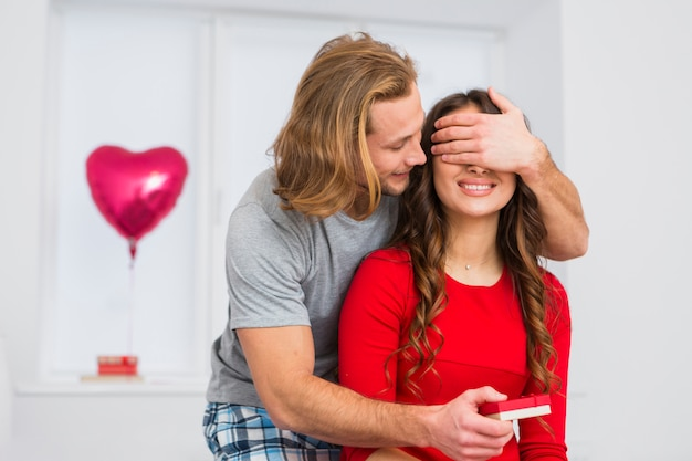 Junger mann des blonden haares, der die augen seiner freundin beim geben von geschenk bedeckt Kostenlose Fotos