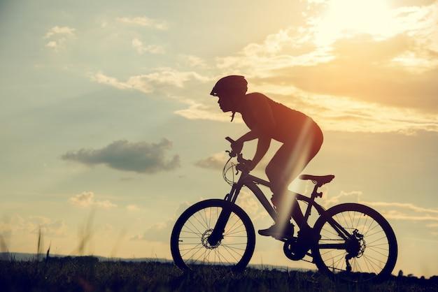 Junger mann des schattenbildes des radfahrens auf sonnenunterganghintergrund Premium Fotos