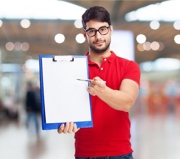 Junger mann, die eine zwischenablage mit einem leeren blatt halten Kostenlose Fotos