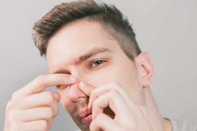 Junger mann drückt akne auf sein gesicht Premium Fotos