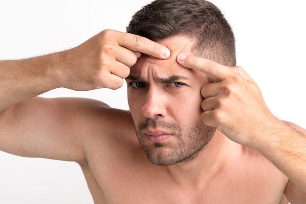 Junger mann drückt pickel auf seiner stirn Kostenlose Fotos