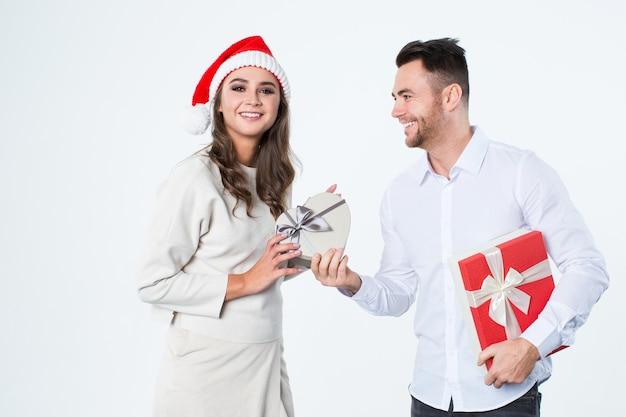 Junger mann gibt geschenke zu einem mädchen auf einem weißen hintergrund. frohes neues jahr und frohe weihnachten. Premium Fotos