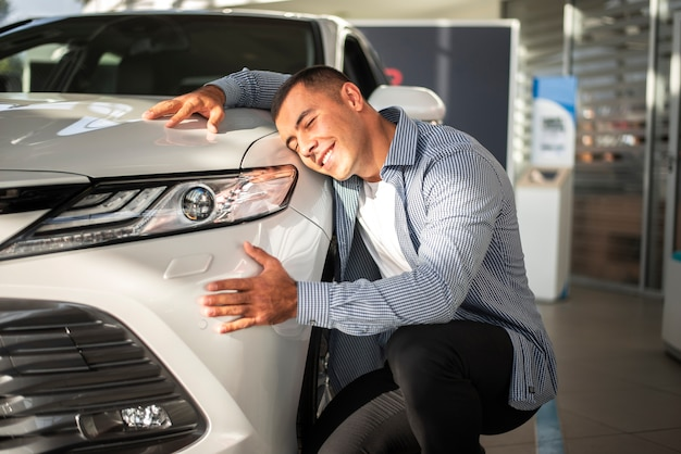 Junger mann glücklich für sein neues auto Kostenlose Fotos
