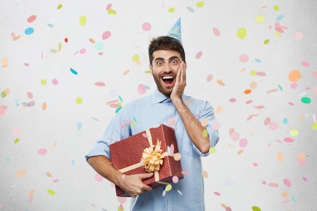 Junger mann hält geschenk umgeben von konfetti Kostenlose Fotos