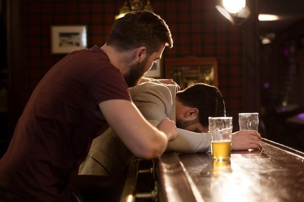 Junger mann hilft seinem betrunkenen freund Kostenlose Fotos