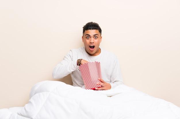 Junger mann im bett mit popcorn Premium Fotos