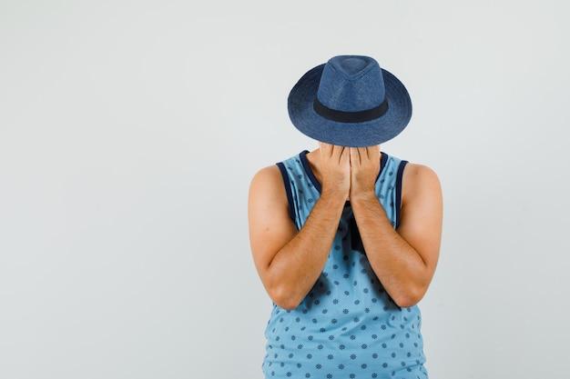 Junger mann im blauen unterhemd, hut, der hände auf gesicht hält und wehmütig aussieht Kostenlose Fotos