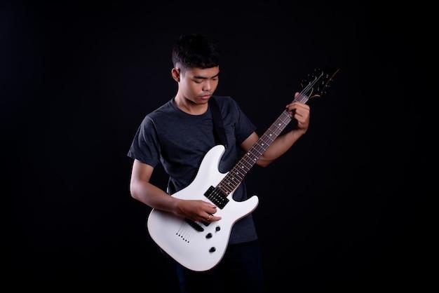 Junger mann im dunklen t-shirt mit e-gitarre Kostenlose Fotos