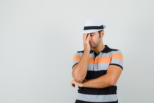 Junger mann im gestreiften t-shirt, hut, der hand auf seinem gesicht hält und müde aussieht Kostenlose Fotos