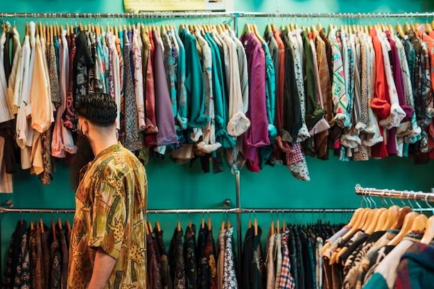 Junger mann im hemd, das kleidung im mall oder im bekleidungsgeschäft wählt Kostenlose Fotos