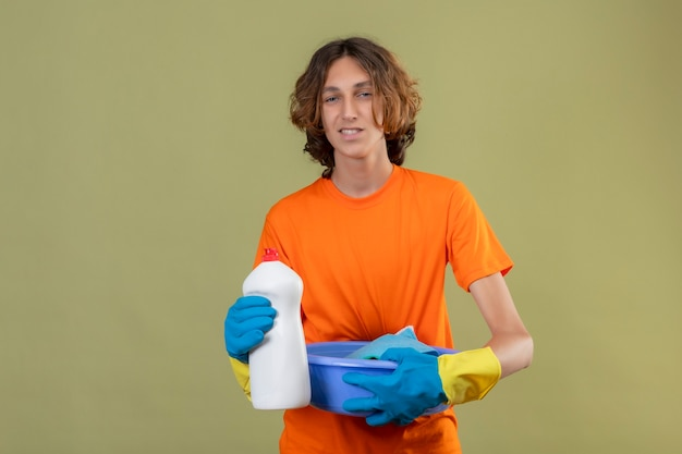 Junger mann im orangefarbenen t-shirt, das gummihandschuhe trägt, die becken mit reinigungswerkzeugen und flasche der reinigungsmittel halten betrachten kamera mit freundlichem lächeln stehen über grünem hintergrund Kostenlose Fotos