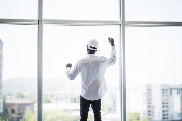 Junger mann im schützenden hemlet, der vor panoramafenstern mit reaierten händen des sieges und des erfolges steht Kostenlose Fotos