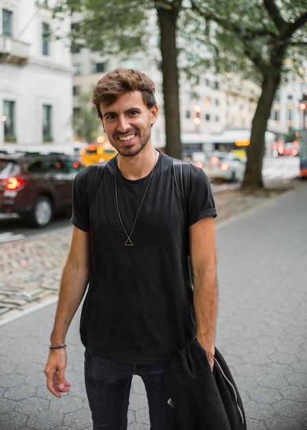 Junger mann im schwarzen lächelnd auf bürgersteig Kostenlose Fotos