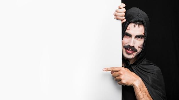 Junger mann im schwarzen mantel mit der haube, die im studio aufwirft Kostenlose Fotos